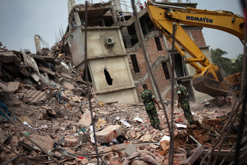 Army personnel watch as workers toil in the collapsed garment factory building, Tuesday, April 30, 2013 in Savar, near Dhaka, Bangladesh. (AP / Wong Maye-E)