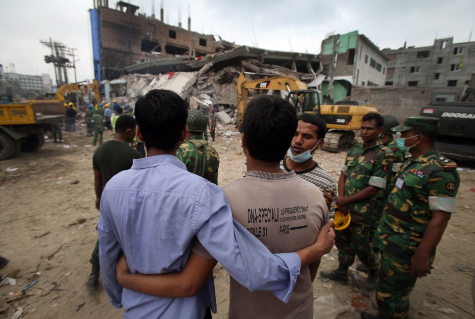 Grieving onlookers comfort each other while workers toil in a collapsed garment factory building on Tuesday, April 30, 2013 in Savar, near Dhaka, Bangladesh. (AP / Wong Maye-E)