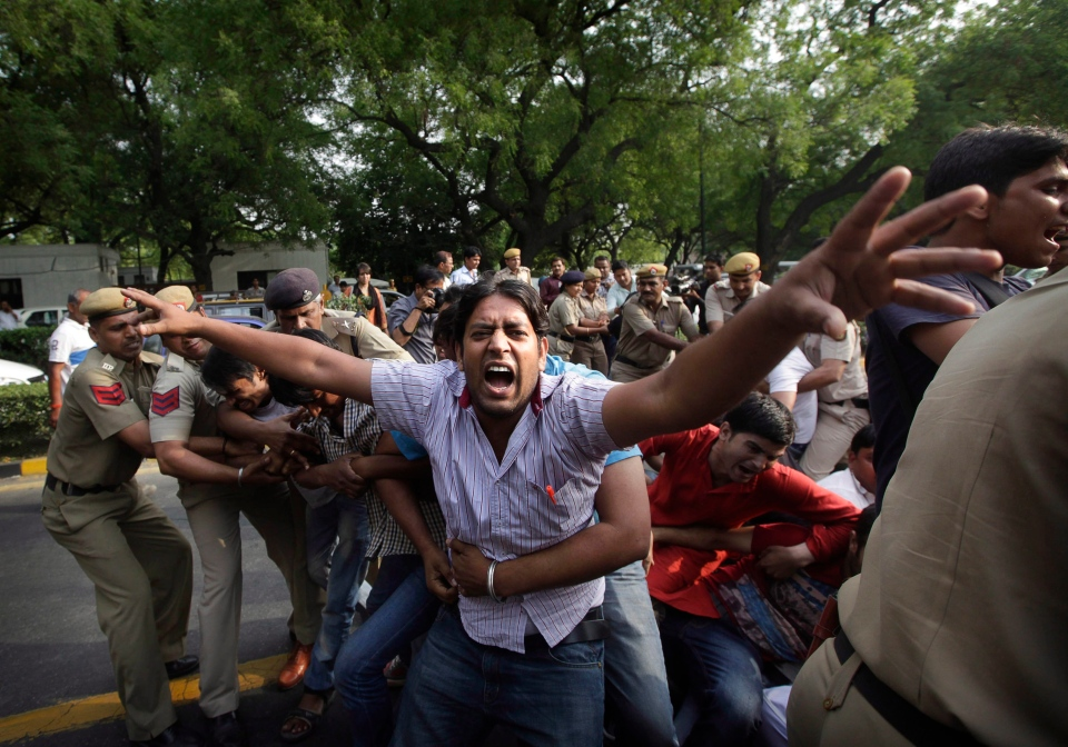 Indian policemen try to remove protestors shouting slogans outside Prime Minister's residence during a protest against the rape of a 5-year-old girl in New Delhi, India, Sunday, April 21, 2013. (AP Photo/Manish Swarup, File)