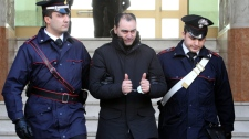 A man identified as Giovanni Pronesti, an alleged member of the 'ndrangheta crime syndicate, salutes his relatives as he is escorted by Italian Carabinieri paramilitary police officers soon after after his arrest in Reggio Calabria, southern Italy, on Tuesday, March 8, 2011. (AP / Adriana Sapone)