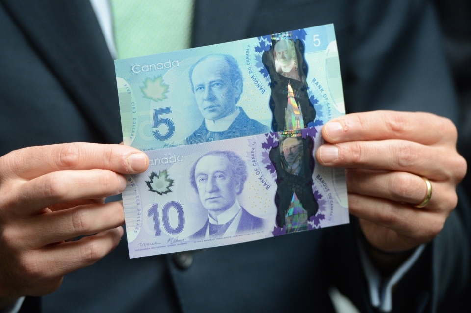 Bank of Canada governor Mark Carney unveils the new polymer $5 and $10 bank notes during a press conference at the Bank of Canada in Ottawa on Tuesday, April 30, 2013. (Sean Kilpatrick / THE CANADIAN PRESS)