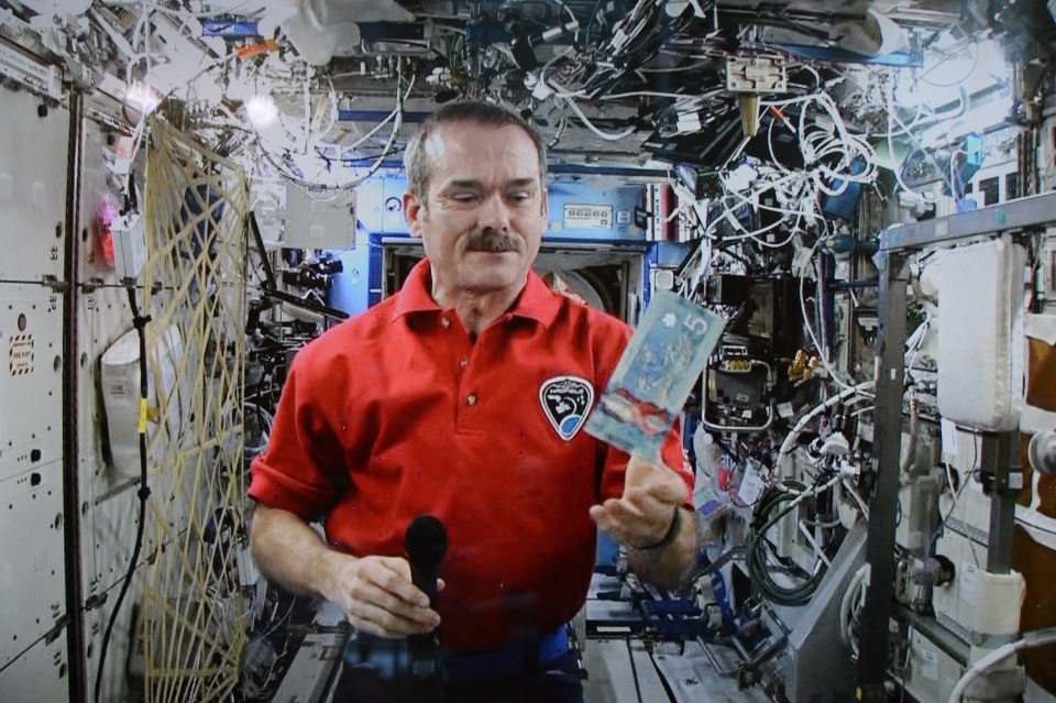 Astronaut Chris Hadfield poses for a photo with a new polymer $5 bank note on Tuesday, April 30, 2013. (Sean Kilpatrick / THE CANADIAN PRESS)