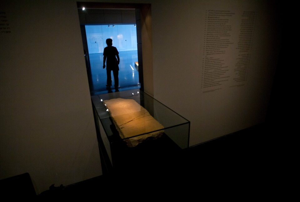 A museum worker walks next to the 'Gabriel Stone' as it is displayed at an exhibition at the Israel Museum in Jerusalem, Tuesday, April 30, 2013. (AP / Sebastian Scheiner)