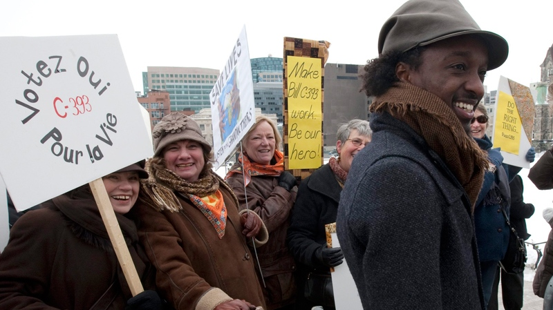 Juno Award-winning artist K'naan speaks with supporters of Bill C-393 after attending a news conference on Parliament Hill in Ottawa, Wednesday March 9, 2011. (Adrian Wyld / THE CANADIAN PRESS)
