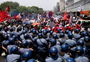May Day moved beyond its roots as an international workers&#39; holiday to a day of international protest Wednesday, with rallies and riots throughout the world demanding wage increases the surge of living costs.<br><br>Protesters, mostly workers, are blocked by police from getting closer to the U.S. Embassy in Manila to mark International Labor Day Wednesday, May 1, 2013 in Manila, Philippines. (AP / Bullit Marquez)