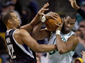 In this Jan. 30, 2013, file photo, Boston Celtics center Jason Collins, right, struggles for control of the ball with Sacramento Kings forward Chuck Hayes (42) during the second half of an NBA basketball game in Boston.