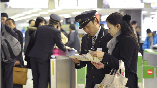Japan Railway Sendai Station staff help stranded bullet train passengers as the high-speed train service is suspended at the station in Sendai, north of Tokyo, following a magnitude 7.2 earthquake hit northern Japan Wednesday, March 9, 2011. (AP Photo/Kyodo News)