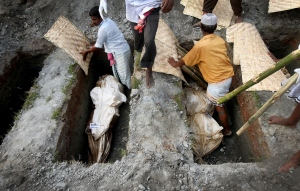 Workers bury unclaimed bodies from the garment factory building collapse in preparation for a mass burial, in Dhaka, Bangladesh, Wednesday, May 1, 2013. (AP / Wong Maye-E)