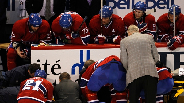 Members of the Montreal Canadiens watch as teammate Max Pacioretty is tended to after taking a hit by Boston Bruins' Zdeno Chara during second period NHL hockey action Tuesday, March 8, 2011 in Montreal. THE CANADIAN PRESS/Paul Chiasson
