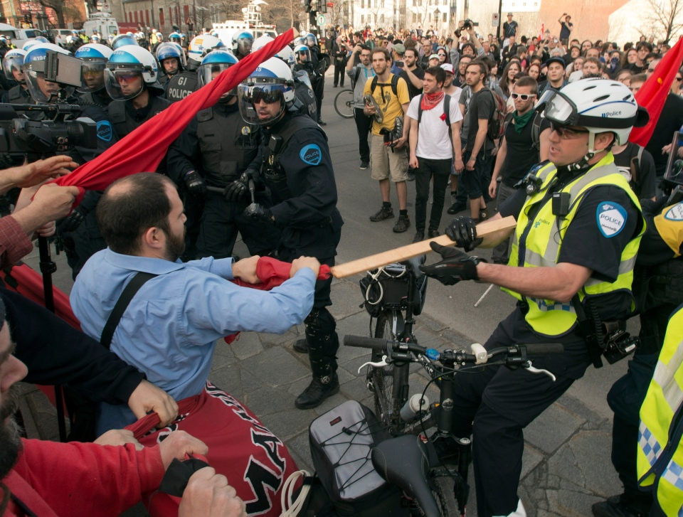 A police officer tries to take a flag away from a protester during a May Day anti-capitalist demonstration Wednesday, May 1, 2013 in Montreal.THE CANADIAN PRESS/Ryan Remiorz
