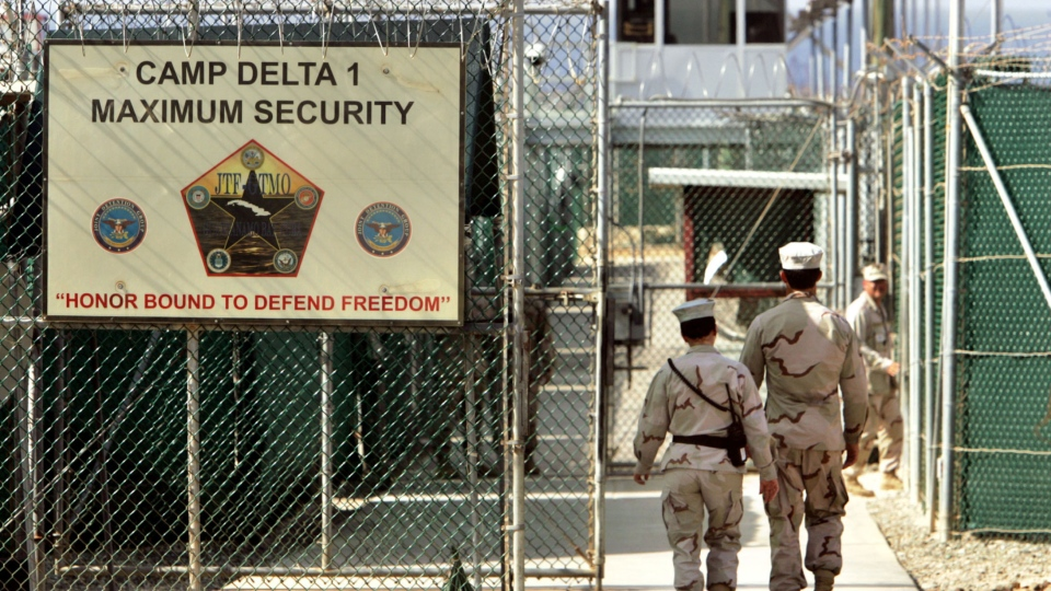 In this June 27, 2006 file photo, reviewed by a US Department of Defense official, US military guards walk within Camp Delta military-run prison, at the Guantanamo Bay US Naval Base, Cuba. (AP / Brennan Linsley, file)