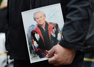 A man holds a photograph signed by George Jones in 1990 while waiting to enter the Grand Ole Opry House for Jones' funeral on May 2, 2013, in Nashville, Tenn. (AP Photo/Mark Zaleski)
