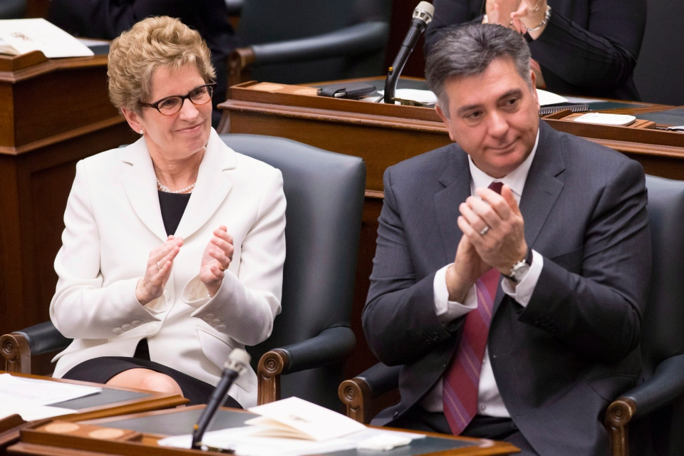 Ontario Premier Kathleen Wynne (left) and Finance Minister Charles Sousa applaud asLieutenant Governor David Onley delivers the throne speech at the Ontario Legislature in Toronto on Tuesday February 19, 2013. (THE CANADIAN PRESS/Chris Young)