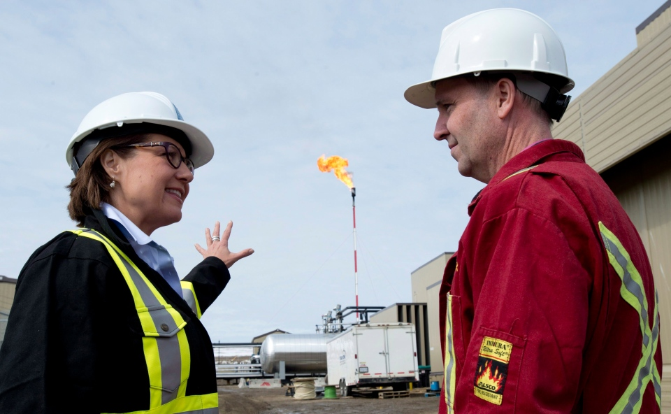 Natural gas is burned off in the background as Liberal leader Christy Clark speaks with local candidate Mike Bernier at the Encana compressor site in Dawson Creek, B.C. Thursday, April 18, 2013. THE CANADIAN PRESS/Jonathan Hayward