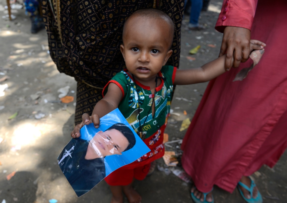 A young child holds a picture of his father who was missing since the collapse of the garment factory building in Savar, near Dhaka, Bangladesh, Thursday, May 2, 2013. (AP / Ismail Ferdous)