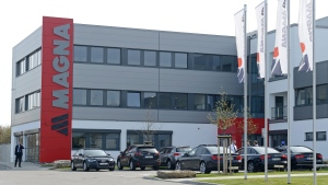 A man walks in front of a new plant of the international automotive supplier Magna in the Magna Exteriors & Interiors (Meerane) GmbH in Meerane, eastern Germany, Wednesday, April 24, 2013. (AP Photo/Jens Meyer)
