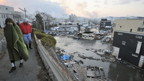 Residents look over destroyed buildings half submerged in water from tsunami in Kesennuma, Miyagi Prefecture, Saturday morning, March 12, 2011 after Japan's biggest recorded earthquake slammed into its eastern coast Friday. (AP Photo/Kyodo News)