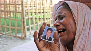 A Bangladeshi woman, holding a photo of her missing son, cries at a graveyard after a garments factory building collapse in Savar near Dhaka, Bangladesh, Friday May 3, 2013. (AP / Palash Khan)
