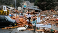 Residents walk through the rubles of residents collapsed by a powerful earthquake in Iwaki, Fukushima prefecture (state), Japan, Friday, March 11, 2011. (Kyodo News)