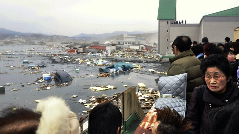 People watch the aftermath of tsunami tidal waves covering a port at Kesennuma in Miyagi Prefecture, northern Japan, after strong earthquakes hit the area Friday, March 11, 2011. (Keichi Nakane / The Yomiuri Shimbun)