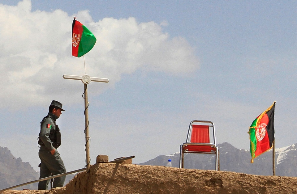 An Afghan policeman stands guard on the roof of a house in the outskirts of Kabul, Saturday, April 6, 2013. (AP / Jawad Jalali)