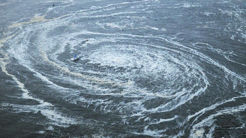 Tsunami swirls near a port in Oarai, Ibaraki Prefecture (state) after Japan was struck by a strong earthquake off its northeastern coast Friday, March 11, 2011. (AP Photo/Kyodo News)