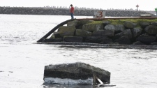A boy watches tsunami surge drag a broken dock section into the boat basin in Crescent City, Calif., Friday, March 11, 2011. (AP / The Times-Standard, Josh Jackson)