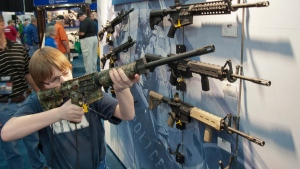 A young man who chose not to give his name sizes-up an assault style rifle during the National Rifle Association's annual convention in Houston on Friday, May 3, 2013. (AP / Steve Ueckert)