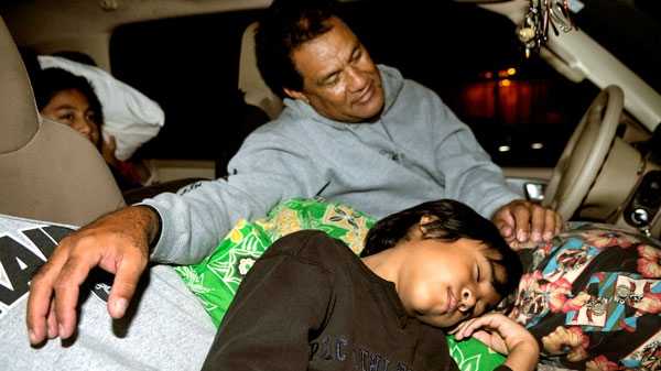 Puipui Faletoi, of Moiliili, Oahu, background center, rests in his vehicle with his sons Daniel, left, and Fletcher Faletoi in the parking lot of Manoa District Park in Oahu, Hawaii, Friday, March 11, 2011. (AP / Rebecca Breyer)