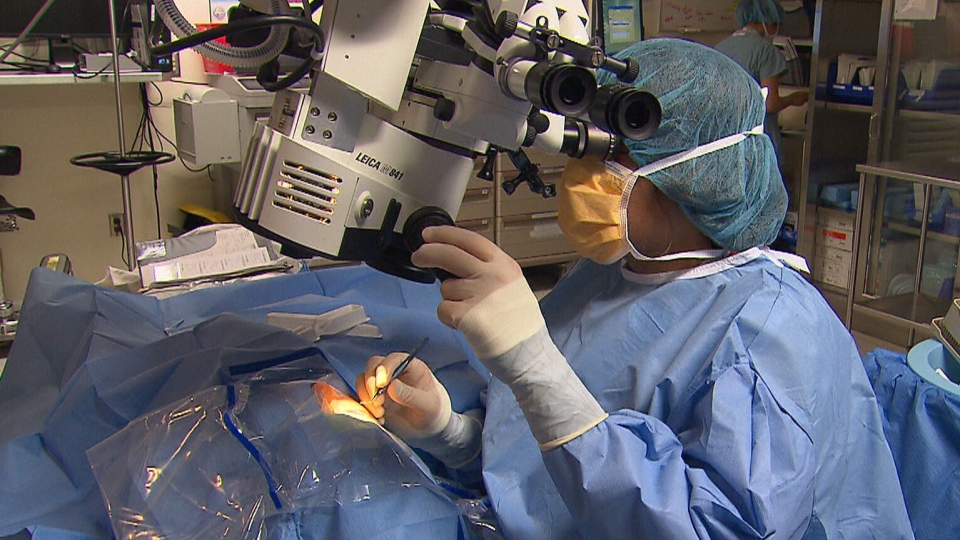 An eye surgeon uses a micro-implant and a magnifier to drain fluid from the eye of a glaucoma patient.