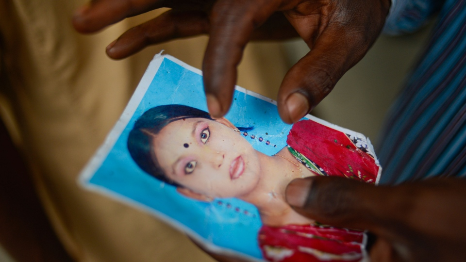 A man holds a portrait of his daughter on Sunday, May 5, 2013 in Savar near Dhaka, Bangladesh, where a garment factory building collapsed last week. (AP / Ismail Ferdous)