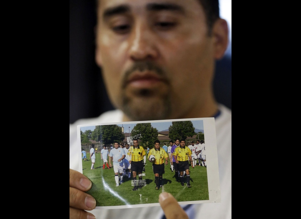 Jose Lopez points to an undated photo of Ricardo Portillo, center, his brother-in-law, following a news conference, at Intermountain Medical Center, in Murray, Utah on Thursday, May 2, 2013. (AP  /Rick Bowmer)