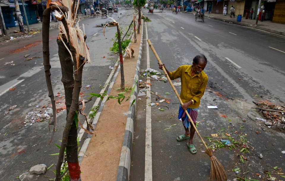 A cleaner sweeps a street after clashes between Bangladesh police and Islamic hardliners during a protest in Savar near Dhaka, Bangladesh, Monday, May 6, 2013. (AP / Ismail Ferdous)