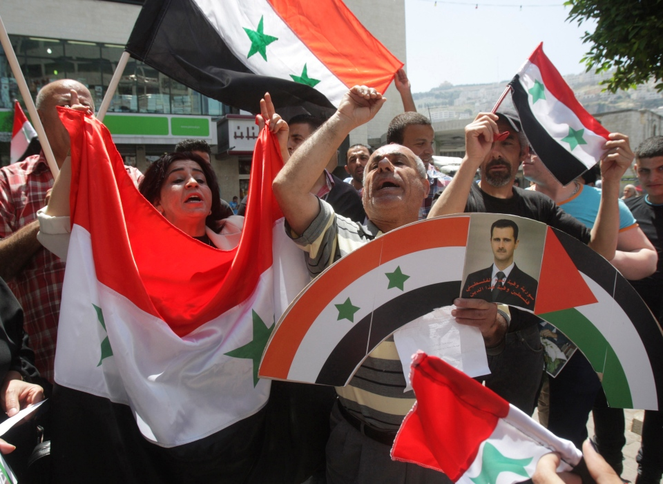 Palestinians hold Syrian flags and a photograph of President Bashar Assad, right, during a march in solidarity with the Syrian regime in the West Bank city of Nablus. Monday, May 6 2013. (AP  / Nasser Ishtayeh)
