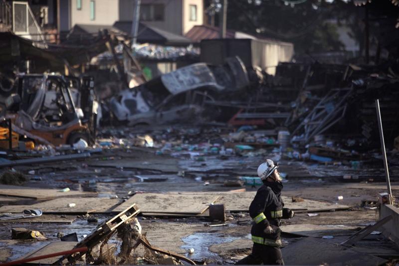 A firefighter runs at the site of a massive tsunami, triggered by a powerful earthquake in Sendai, Miyagi prefecture, northern Japan, Saturday, March 12, 2011. (AP / Junji Kurokawa)