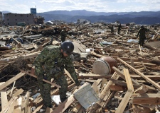 Rescue workers look for survivors while going through debris in Rikuzentakada People in Iwate Prefecture (State), Saturday morning, March 12, 2011, a day after a strong earthquake-triggered devastating tsunami hit the northern Japan. (The Yomiuri Shimbun / Masamine Kawaguchi)