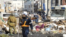 Japanese soldiers and rescue workers try to remove rubble on a street in Kamaishi, northeastern Japan, on Saturday March 12, 2011. (AP / Kyodo News)