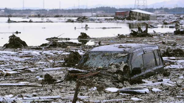 A vehicle is seen buried in mud and debris after it was washed away by the tsunami in Sendai, northern Japan, Saturday, March 12, 2011. (AP / Kyodo News)