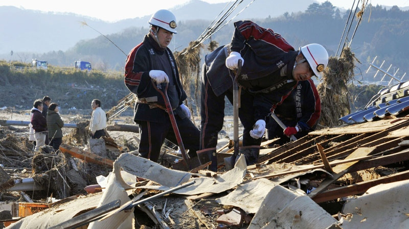 Local fire company members search through a home collapsed by Friday's powerful earthquake-triggered tsunami during a search operation at Yamamoto town, Miyagi prefecture, Saturday, March 12, 2011. (AP / Kyodo News)