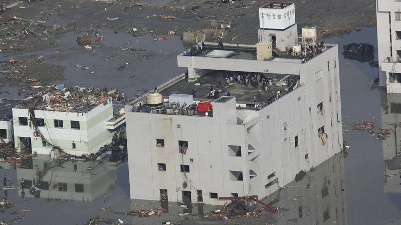 People are stranded on the top of a building in Minami Sanriku, Miyagi, northern Japan Saturday, March 12, 2011 following Friday's catastrophic earthquake and tsunami. (AP / Yomiuri Shiimbun, Naoki Ueda)