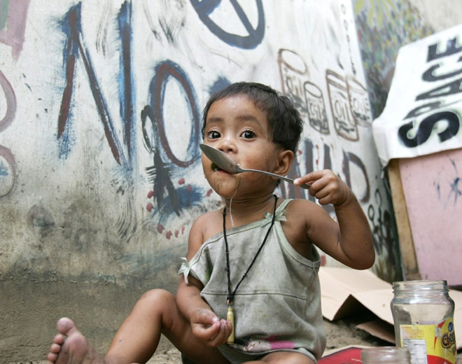 A homeless girl eats her lunch next on a street in Manila's Quezon City in the Philippines on Friday, April 18, 2008. (AP / Bullit Marquez)
