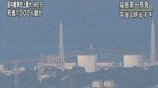 In this image made from Japan's NHK television, an aerial view shows the Fukushima Daiichi power plant's Unit 1, only frames are seen at left, in Okumamachi, Fukushima prefecture, Japan, Saturday, March 12, 2011. The walls of the building at the nuclear power station crumbled Saturday as smoke poured out. (AP Photo/NHK TV)