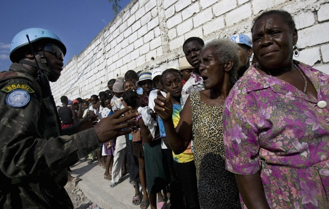People wait for food at a UN distribution center in Port-au-Prince, Friday, April 18, 2008. (AP / Ariana Cubillos)
