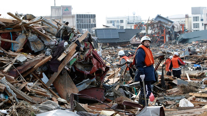 Volunteer firefighters search for victims of Friday's tsunami at Rikuzentakada, Iwate Prefecture, northern Japan, Sunday, March 13, 2011. (AP / Shizuo Kambayashi)