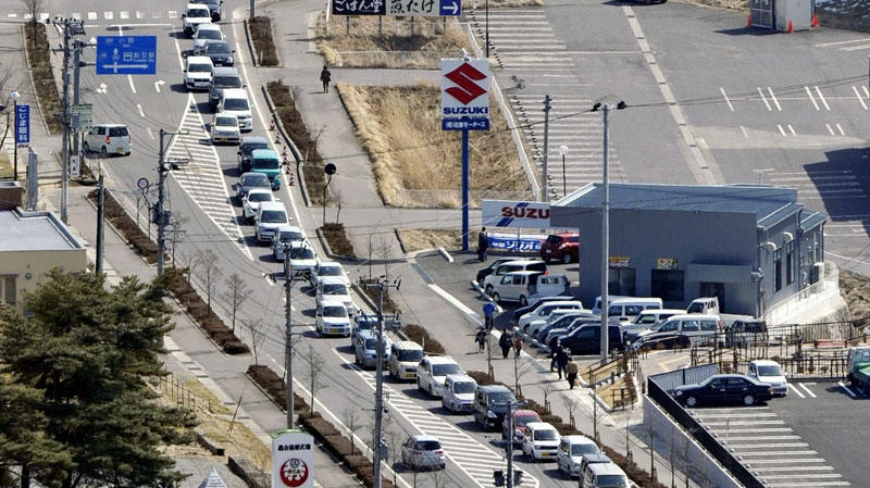 A road is jammed with evacuating vehicles following an order to evacuate the area covering a radius of 20 kilometers around the Fukushima Dai-ichi power plant, in Tamura, Fukushima, northern Japan Sunday, March 13, 2011. (AP / Kyodo News)