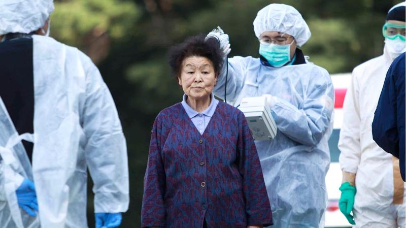 Residents evacuated from areas surrounding the Fukushima nuclear facilities damaged in Friday's massive earthquake, are checked for radiation contamination in Koriyama city, Fukushima Prefecture, Japan, Sunday, March 13, 2011. (AP / Wally Santana)