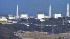 Unit 1 reactor of the Fukushima Daiichi Nuclear Power Plant, left, with its top part of walls blown off after Saturday's explosion is seen with other units including Unit 3 reactor, second from right, where a hydrogen explosion could occur in Okumamachi, Fukushima Prefecture in Japan, Sunday, March 13, 2011. (AP / Kyodo News, Masaru Nishimoto)