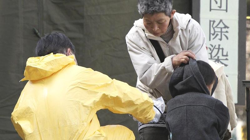 A boy has his radiation level checked in the compound of Fukushima Gender Equality Centre in Nihonmatsu, Fukushima Prefecture, northeastern Japan, Sunday, March 13, 2011. (AP / The Yomiuri Shimbun, Daisuke Tomita)