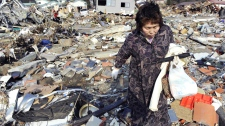 A woman searches through the rubble of her home destroyed in Friday's powerful earthquake-triggered tsunami in Ofunato, Iwate Prefecture, northern Japan, Sunday, March 13, 2011. (AP / Kyodo News)