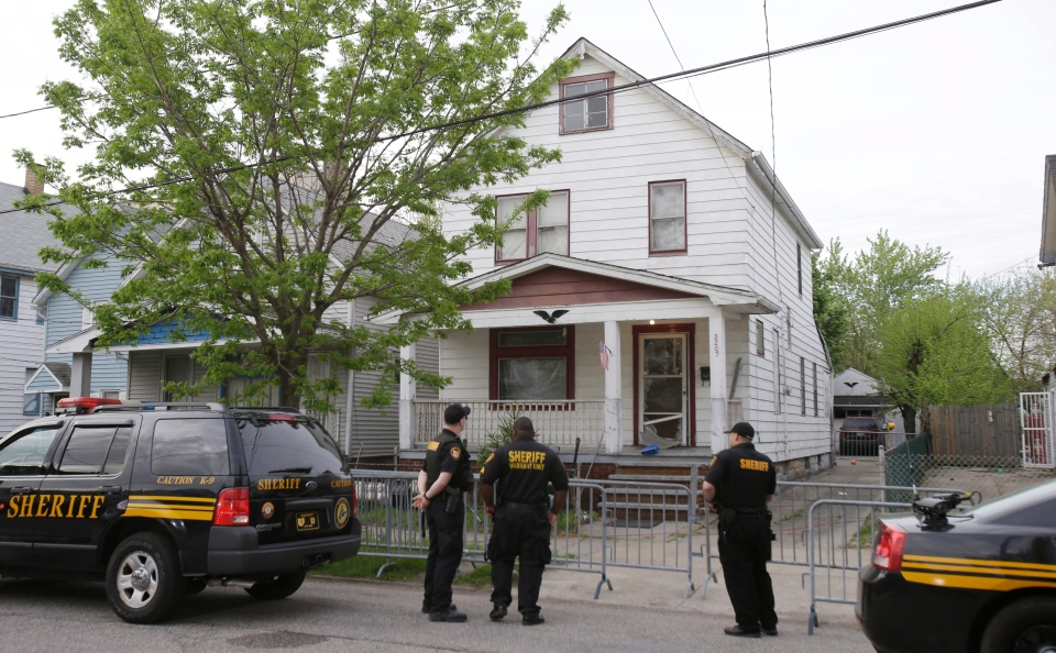 Sheriff deputies stand outside a house in Cleveland the day after ...
